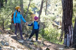 A woman walks with her son through the forest. The boy with his mother go hiking. A child with a backpack is in the park. Travel with children. The kid holds mom's hand. Mountain trail.