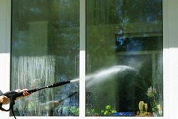 A woman washes a window with a spray under high pressure. Indoor plants are visible through the glas