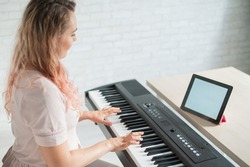 A woman watches video lessons on a digital tablet and plays on an electro synthesizer. The girl learns to play the piano remotely.