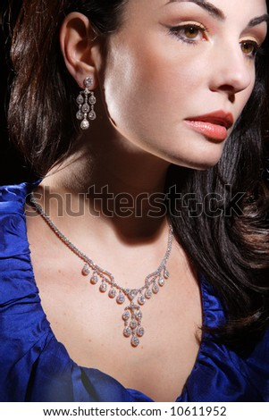 A woman wearing a diamond necklace and matching earrings