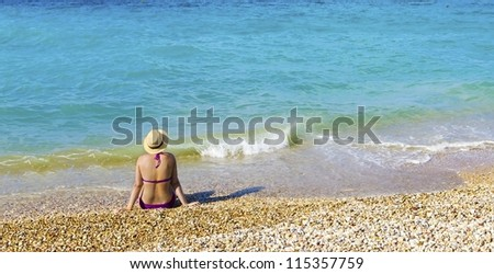A woman wearing a hat, sitting on the beach staring at the sea