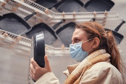 A woman wearing a medical mask buys a frying pan in a store