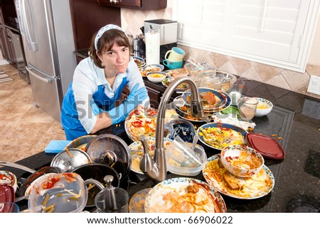 stock photo : A woman wearing dish washing gloves and an apron contemplates doing the dishes.