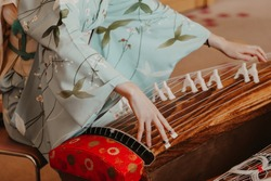 A woman wearing kimono is playing a traditional Japanese musical instrument  Koto, a Japanese harp.