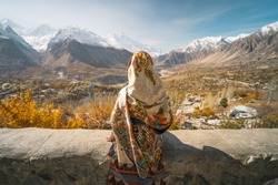 A woman wearing traditional dress sitting on wall and looking at Hunza valley in autumn season, Gilgit Baltistan in Pakistan, Asia