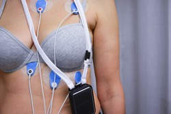 A woman wears a General Electric brand Seer Light Holter, an ambulatory electrocardiography device, to monitor the electrical activity of her cardiovascular system. Health, disease concept. Real foto.