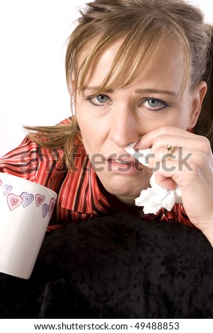 A woman who has a cold and is sick holding a warm drink while wiping her nose.