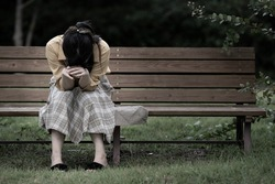 A woman who is depressed on the bench.