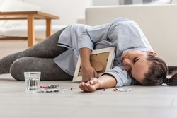 A woman who loss a close person in her life overdosed by pills and lost consciousness, lying on the floor.