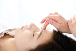 A woman who receives acupressure between eyebrows in an acupuncture clinic
