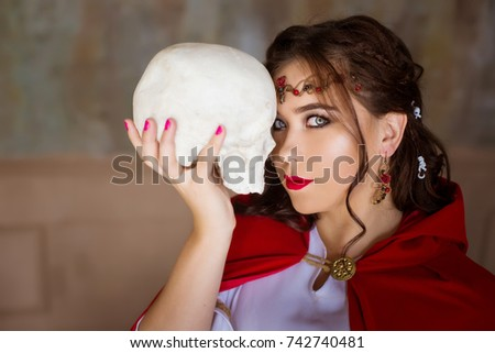 Stock Photo A woman witch in an old suit is holding a white skull of plaster.