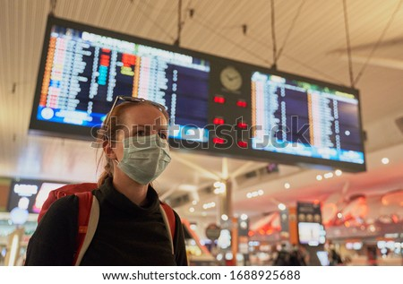 A woman with a backpack wearing an anti-virus mask on her face at the airport arrivals board
