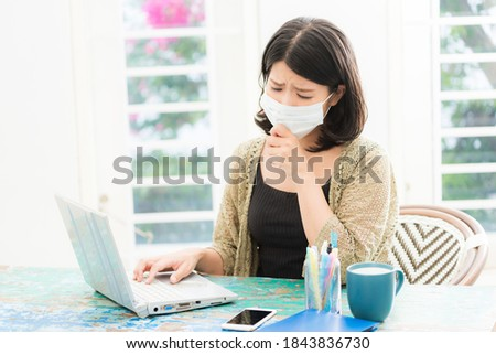 a woman with a bad physical condition wearing a mask sitting in front of a computer Stock photo ©
