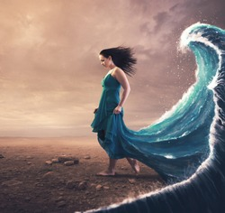 A woman with a blue dress and large wave behind her.