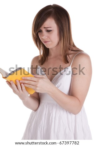 A woman with a confused and sad expression on her face reading her yellow book.