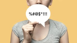 A woman with a conversational cloud in her hand and an obscenity symbol on it. Ban on swearing, obscenities