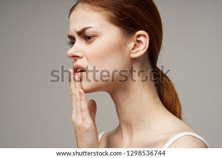 A woman with a displeased facial expression is holding a hand near the mouth on a gray background health problems #1298536744