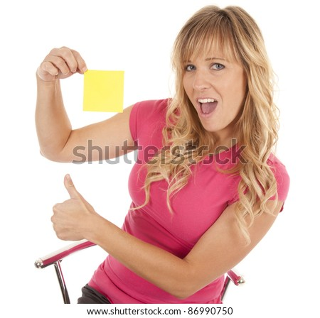 A woman with a excited expression on her face with a thumb up holding a note.