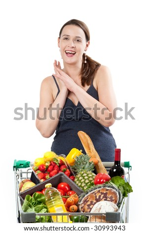 A woman with a full shopping cart happy to be shopping - clasping hands on a white background