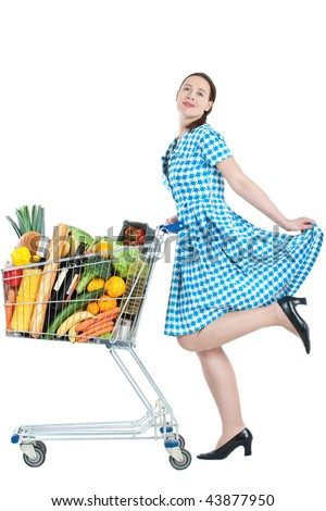 A woman with a full shopping cart happy to be shopping - on a white background