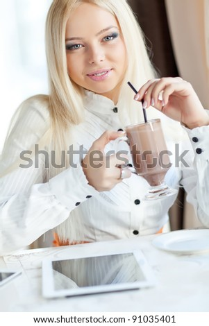 A woman with a laptop in a cafe with a cup of coffee.