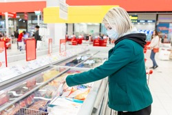 A woman with a mask on examining a frozen good in the refridgerated goods at a supermarket. Shopping during the pandemic. Checking the expiration date.