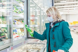 A woman with a mask on examining a frozen good in the refridgeratoed goods area at a supermarket. Shopping during the pandemic. Checking the expiration date.