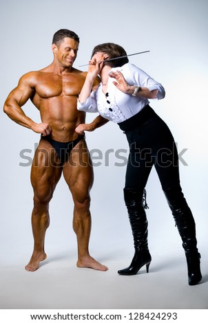 A woman with a pointer next to a bodybuilder.