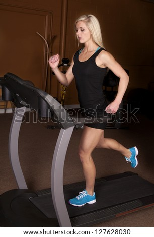 A woman with a serious expression and running on her treadmill.