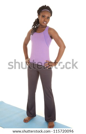 A woman with a serious expression standing on her mat with her hands on her hips - stock photo