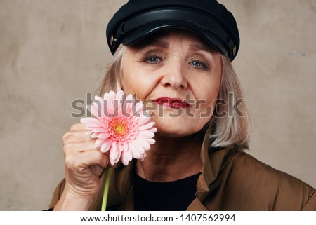 A woman with a short haircut and in a brown coat with a pink flower in front of her face is smiling into the camera a cropped look  #1407562994