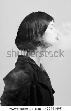 A woman with a short haircut and in dark clothes emits smoke from her mouth #1499441495