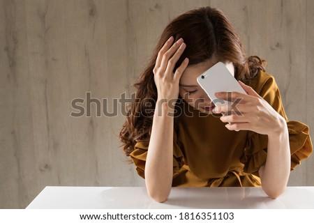 A woman with a smartphone is sad. Сток-фото ©