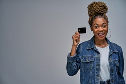 A woman with a smile in earrings holding a credit card by fingers in hands.