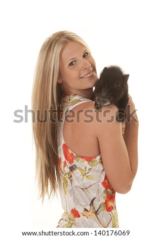 a woman with a smile on her face holding her baby pig on her shoulder.
