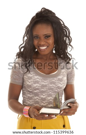 a woman with a smile on her face holding on to a book.
