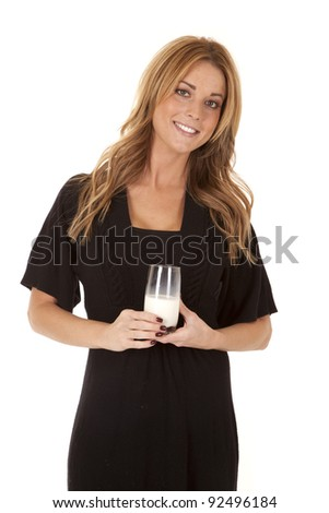 A woman with a smile on her face holding on to her glass of milk.