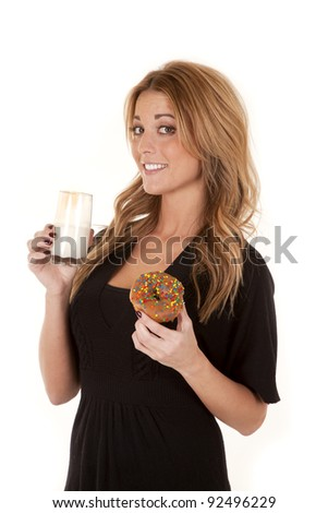 A woman with a smile on her face holding on to her milk and donut.
