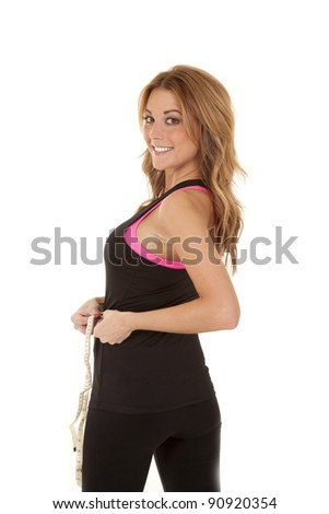 a woman with a smile on her face looking over her shoulder as she is measuring her waist.