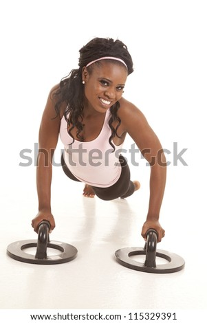 A woman with a smile on her face using push up bars.