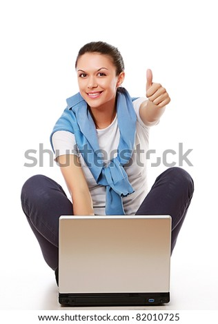 A woman with a thumb up sign working with a laptop on the floor, over white