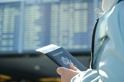 A woman with a US passport and boarding pass in the hands of the airport departure board