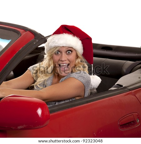 A woman with a very excited expression on her face driving while she is wearing her Santa hat.