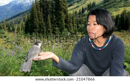 A woman with a whiskey jack in Garibaldi Provincial Park, British Columbia, Canada.