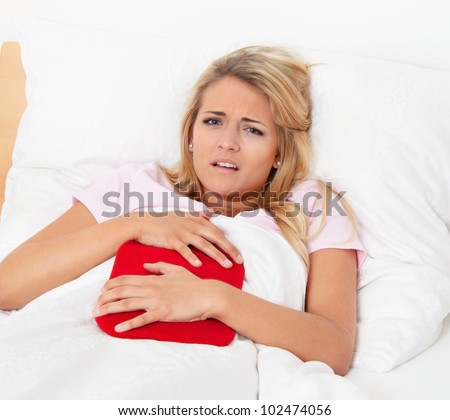 a woman with abdominal pain in bed and has a hot water bottle