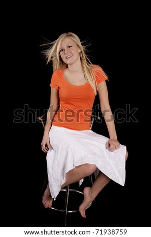 A woman with an orange top and white skirt is sitting in a chair.