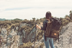A woman with backpack climbing and standing on top of mountain with success. Travel and Summer Concept.