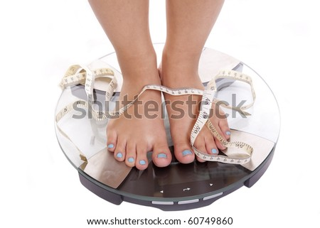 A woman with blue toenails is standing on the scales measuring her weight.