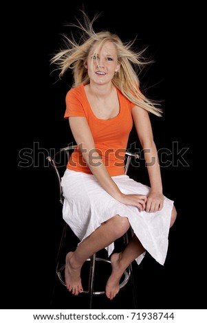 A woman with crazy hair is sitting on a stool.