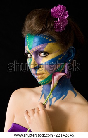 A woman with extreme full-face body painting poses on a black background holding a calla lily. Mardi Gras color theme.